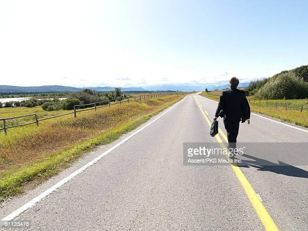 Businessman walks along center line on rural road