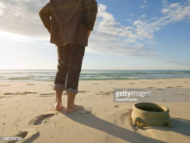businessman walks barefoot in the sand - decorative urn stock pictures, royalty-free photos & images
