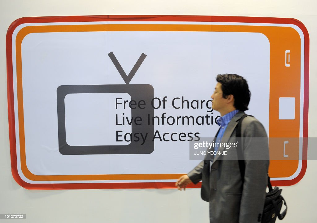 A businessman walks past an advertising board for the smart phone during the World IT Show in Seoul on May 28, 2010.