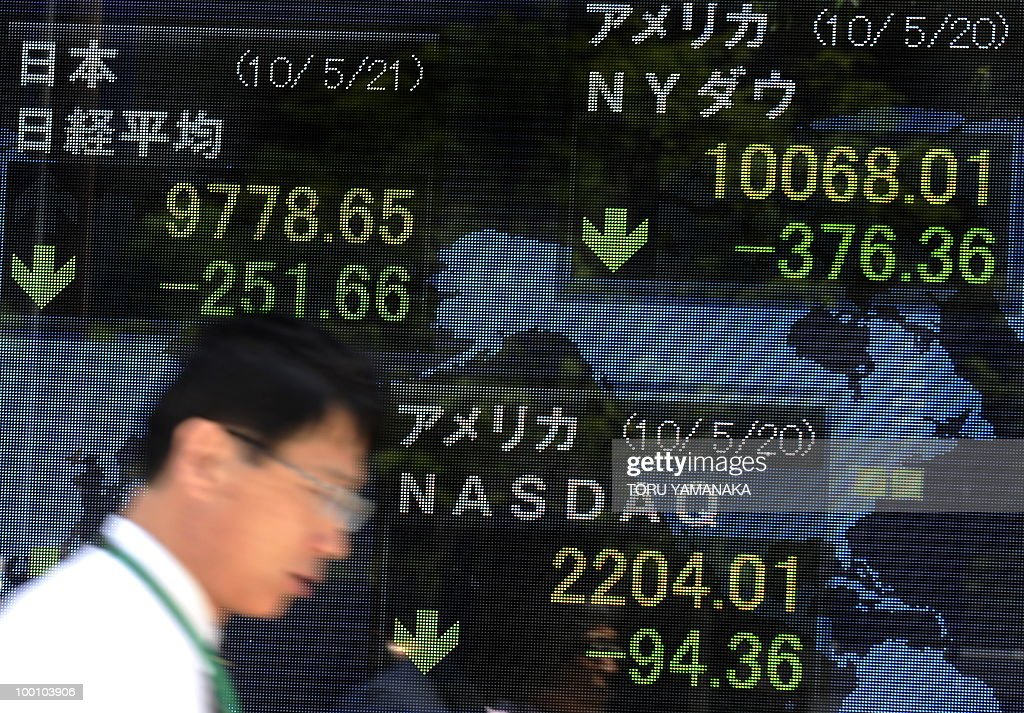 A businessman walks past an electric quotation board flashing key indexes of stock exchanges in the world in front of a securities company in Tokyo on May 21, 2010. Japanese shares plunged 2.51 percent by noon following Wall Street's biggest drop in more than a year and as the continued strength of the yen prompted investors to sell shares. AFP PHOTO/Toru YAMANAKA