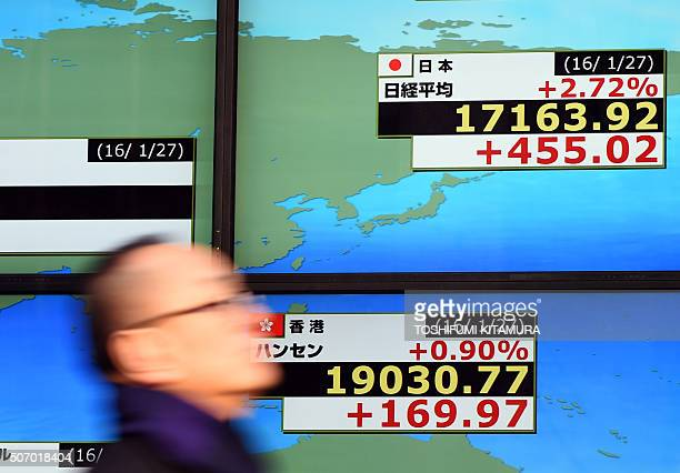 A businessman walks past an electronic monitor showing the numbers on the Tokyo Stock Exchange and Hong Kong Stock Exchange in Tokyo on January 27...