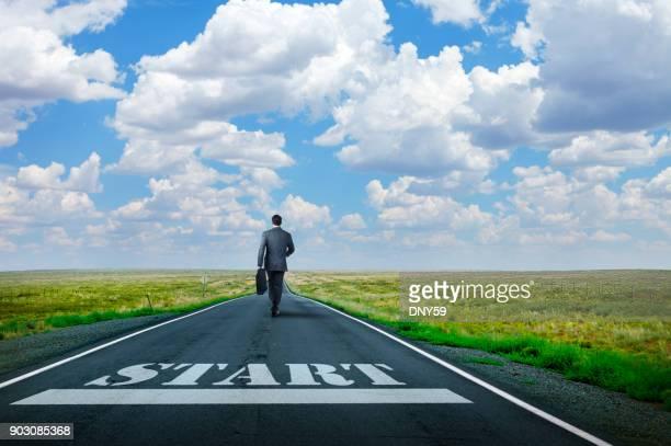 長い田舎道に描かれたスタート ラインを過ぎて歩くビジネスマン