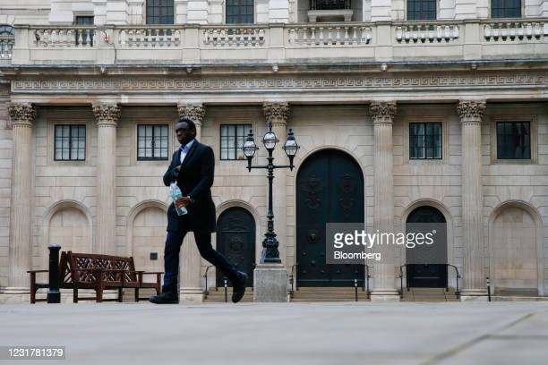 Businessman walks past the Bank of England in the City of London, U.K., on Thursday, March 18, 2021. The Bank of England is likely to emphasize its...