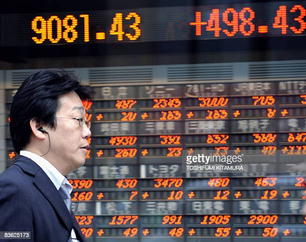 Businessman walks past the stock indicator flashing Tokyo stock's closing rate in central Tokyo, on November 10, 2008. Nikkei stock index rose 498.43...
