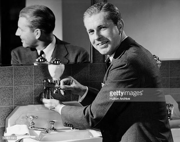 Businessman washing hands, portrait (B&W)