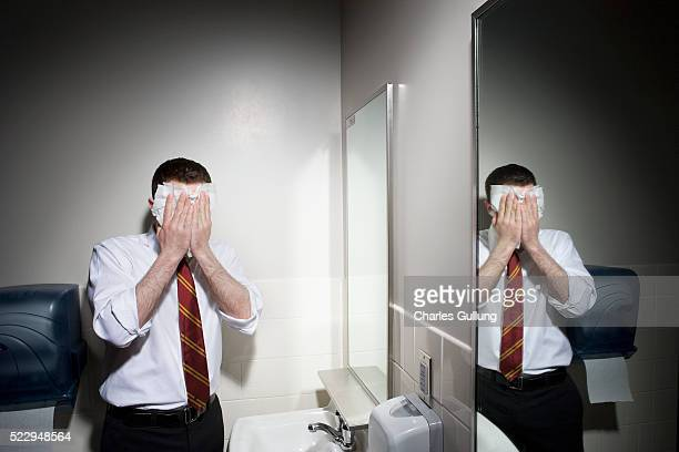 Businessman Washing His Face in Restroom