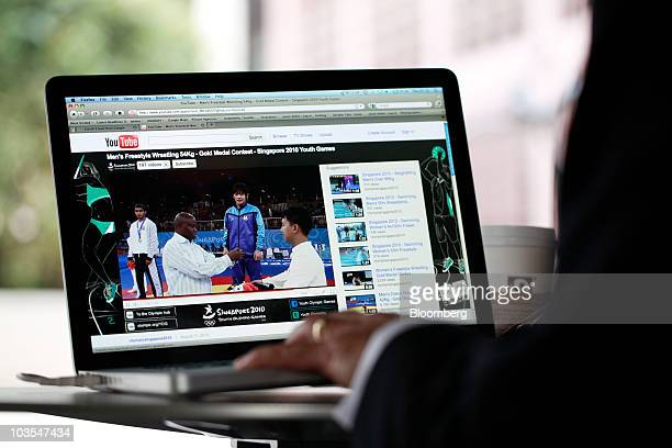 A businessman watches a video clip on Google Inc�s YouTube website using an Apple Macbook Pro laptop computer made by Apple Inc in this arranged...