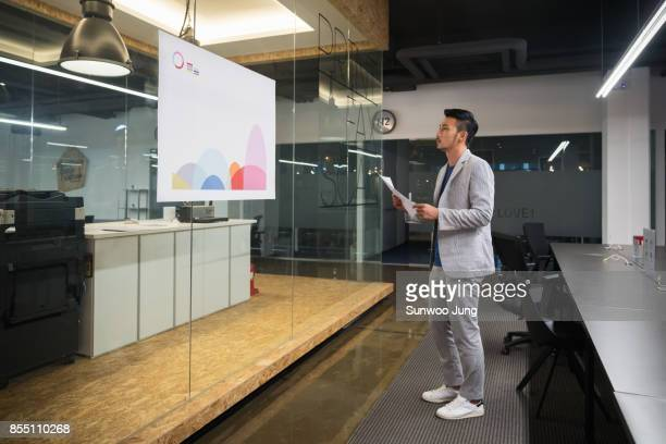 businessman watching a creative graph in modern office - trousers stock pictures, royalty-free photos & images