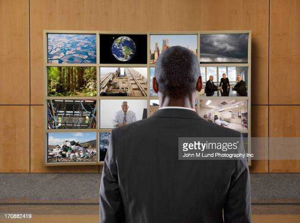 Businessman watching collage screen in office