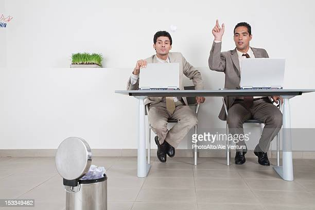 Businessman watching colleague throwing paper ball at garbage can