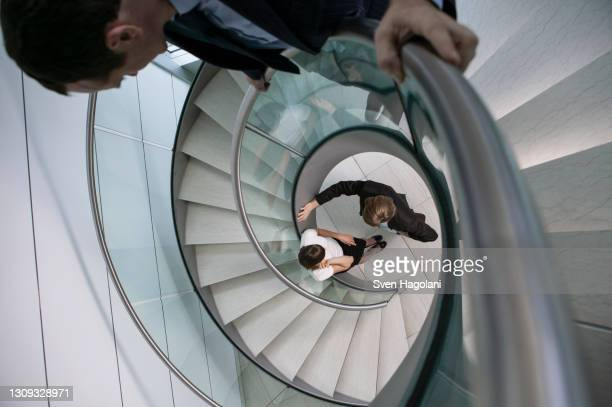 businessman watching colleagues talk at bottom of spiral staircase - taking a corner stock pictures, royalty-free photos & images