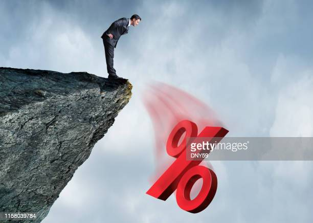 businessman watching interest rates fall off a cliff - percentage sign stock pictures, royalty-free photos & images