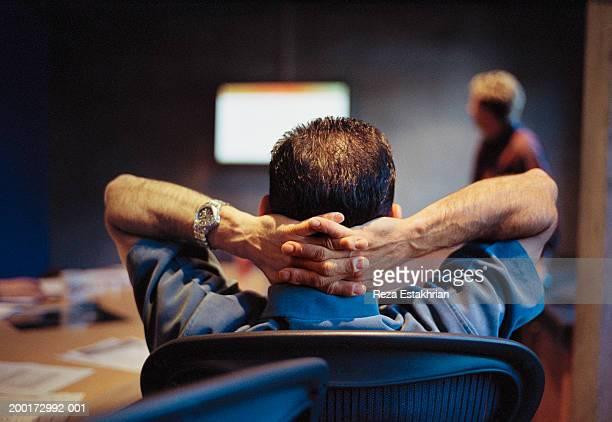Businessman watching presentation, hands behind head