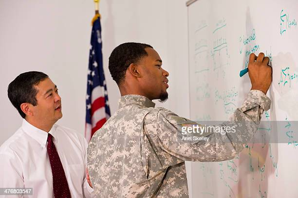 businessman watching soldier writing on whiteboard - military training stock pictures, royalty-free photos & images