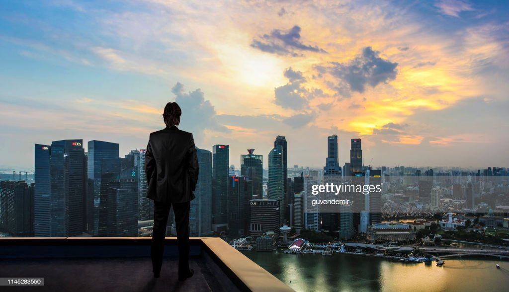 Businessman watching the city on the rooftop of skyscraper : Stock Photo