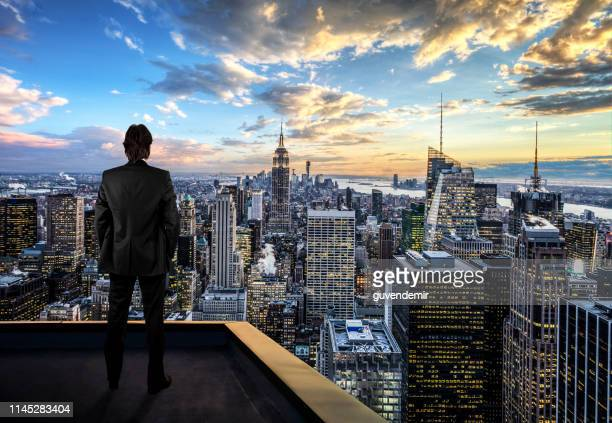 businessman watching the new york city on the rooftop of skyscraper - la via giusta foto e immagini stock