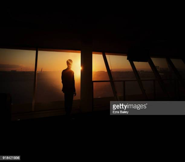 Businessman watching the sunrise in an airport.