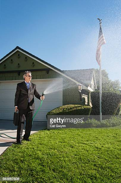 Businessman watering lawn in business suit