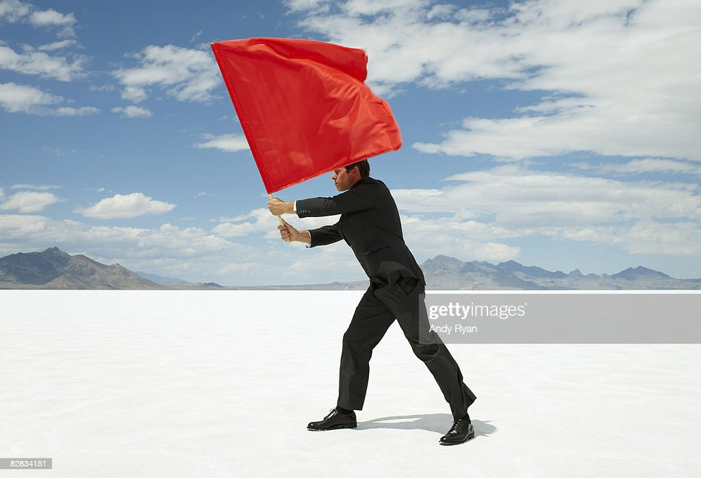Businessman Waving Red Flag on Salt Flat : Stock Photo