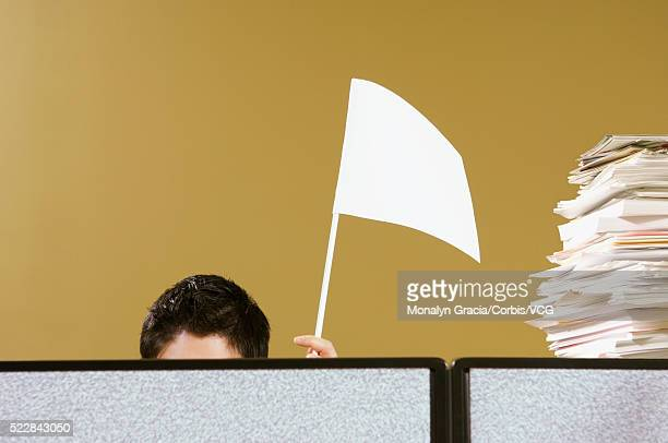 Businessman waving white flag from behind cubicle