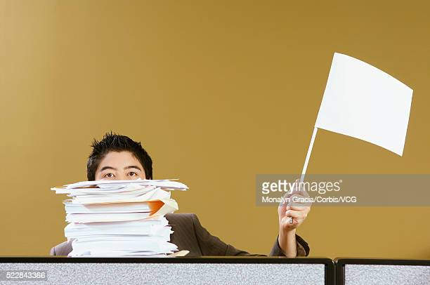 Businessman waving white flag