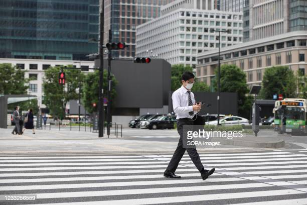Businessman wearing a face mask as a preventive measure against the spread of covid-19 crosses the street in front of Tokyo Station. The State of...