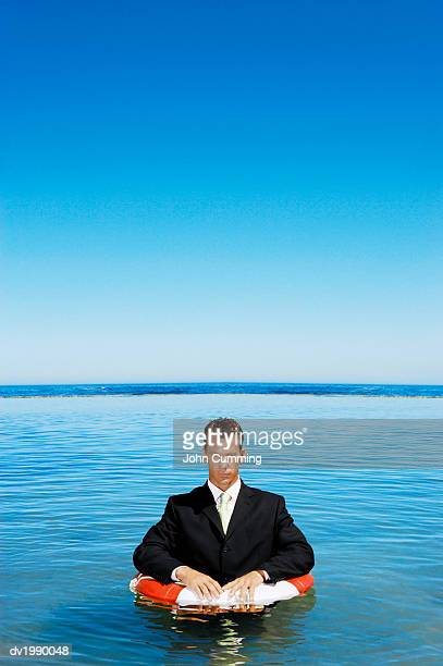 businessman wearing a full suit and floating in the sea with a rubber ring - out of context stock pictures, royalty-free photos & images