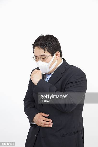 A businessman wearing a mask coughs.