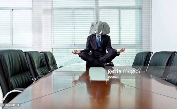 businessman wearing a mask meditating on conference table - businesswear stock pictures, royalty-free photos & images