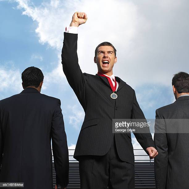businessman  wearing a medal and shouting with his arms raised
