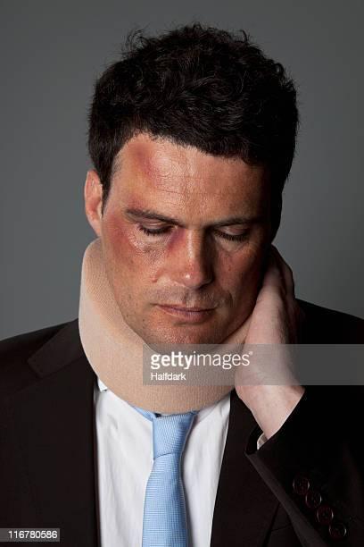 A businessman wearing a neck brace