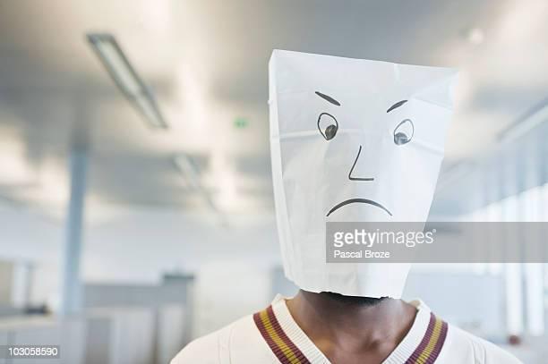 Businessman wearing a paper bag of sad face