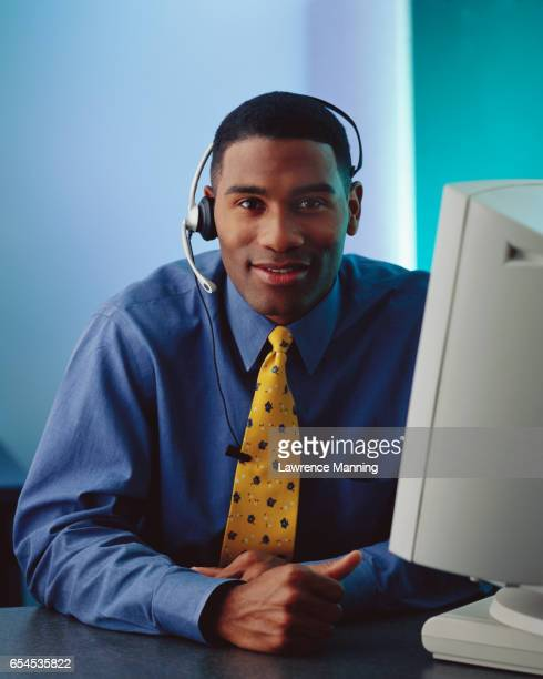 Businessman Wearing a Phone Headset at a Computer