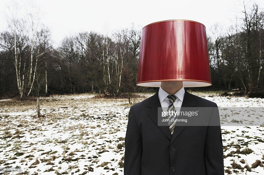Businessman Wearing a Red Lamp Shade on His Head in a Forest : Stock Photo