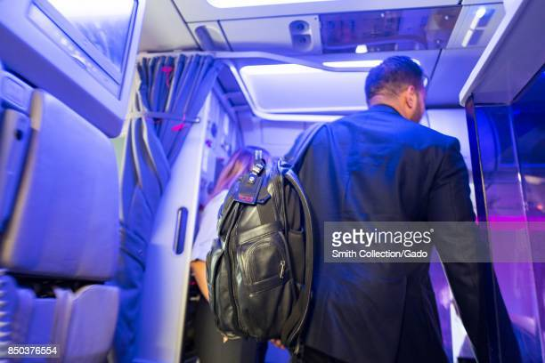 A businessman wearing a suit and a Tumi suitcase boards a Virgin America airplane with distinctive purple 'mood lighting' visible at San Francisco...