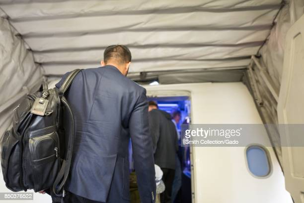 A businessman wearing a suit and carrying a Tumi suitcase prepares to board a Virgin America airplane at San Francisco International Airport San...