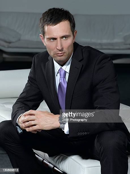 Businessman wearing a suit, sitting on a white sofa