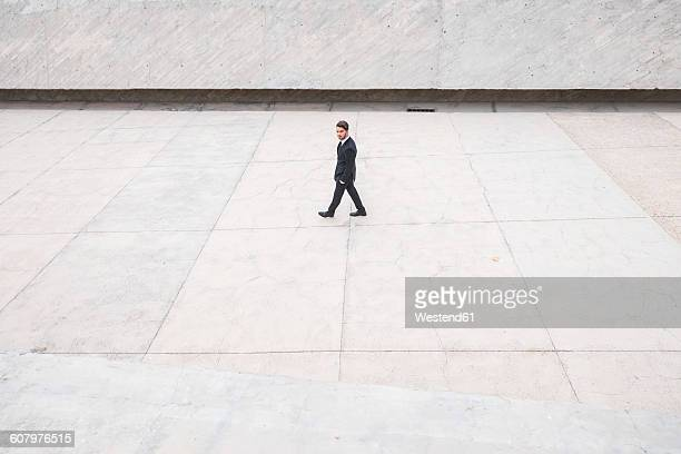 Businessman wearing black suit passing