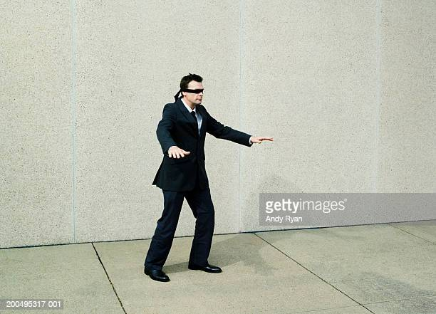 Businessman wearing blindfold walking aimlessly on sidewalk