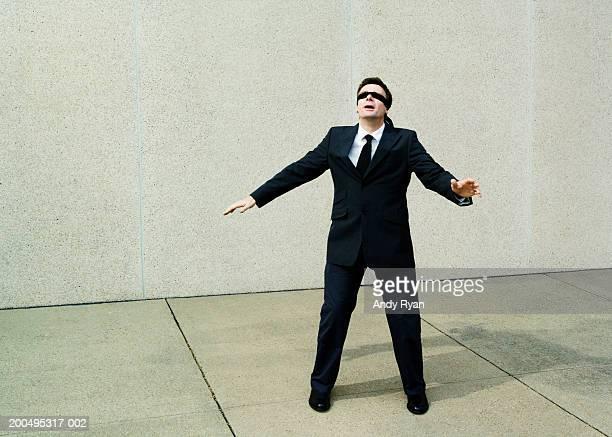 Businessman wearing blindfold walking aimlessly on sidewalk