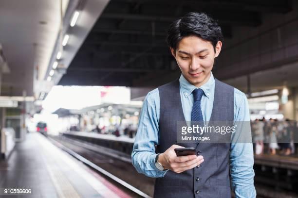 Businessman wearing blue shirt and vest standing on train station platform, holding mobile phone.