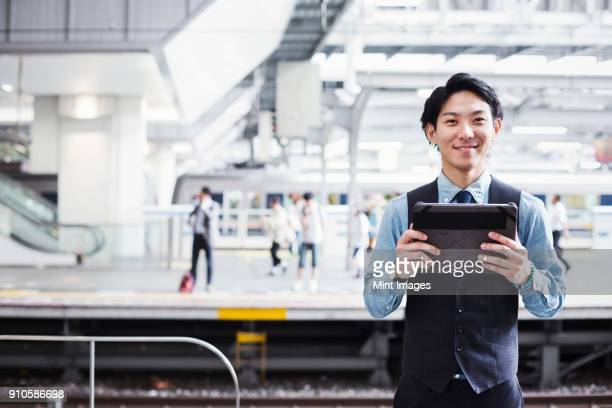 businessman wearing blue shirt and vest standing on train station platform, holding digital tablet, looking at camera. - 鉄道のプラットホーム ストックフォトと画像