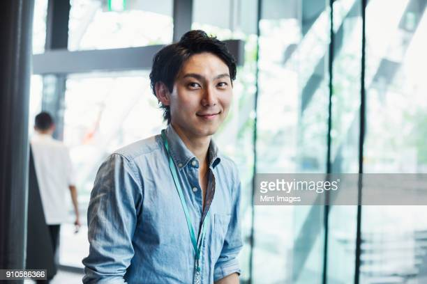 businessman wearing blue shirt standing indoors by glass wall, looking at camera. - 20代 ストックフォトと画像