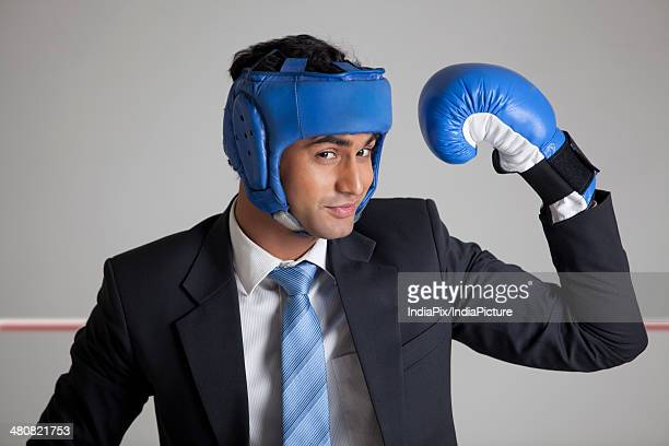 Businessman wearing boxing gloves and headwear flexing muscles in boxing ring