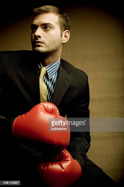 Businessman Wearing Boxing Gloves, On Brown Background