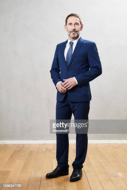 businessman wearing dark blue suit - staan stockfoto's en -beelden
