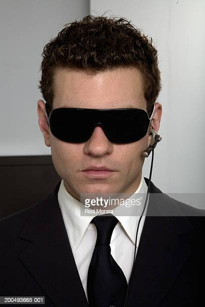 Businessman wearing dark glasses and hands free mobile phone device