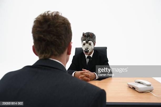 Businessman wearing donkey mask conducting interview