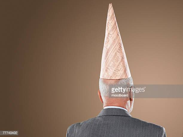 businessman wearing dunce cap - dunce's hat stock pictures, royalty-free photos & images