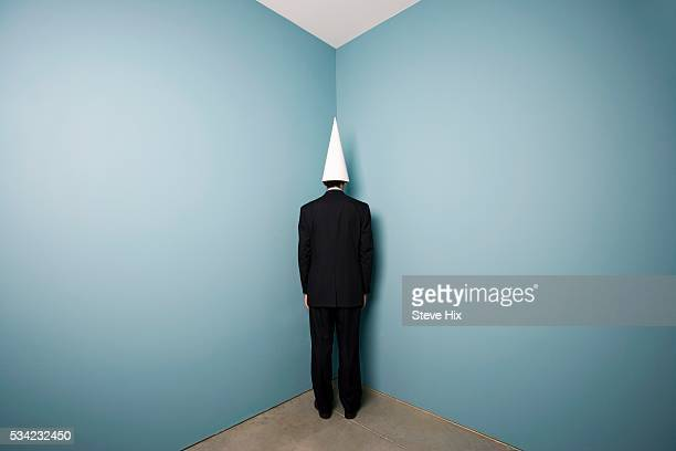 businessman wearing dunce cap standing in corner - dunce's hat stock pictures, royalty-free photos & images